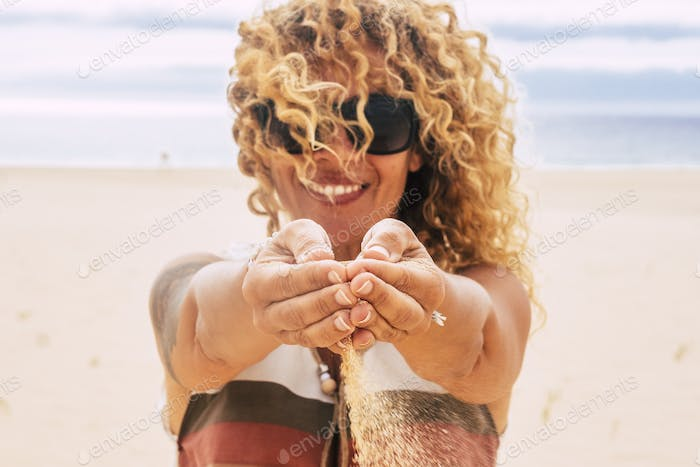 Cheerful and beautiful young caucasian woman play with the sand