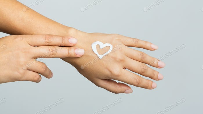 Body care. Cream in heart shape on female hand