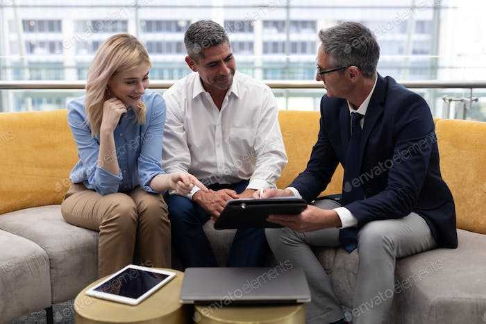 Business executives discussing over digital tablet sitting on the sofa in modern office