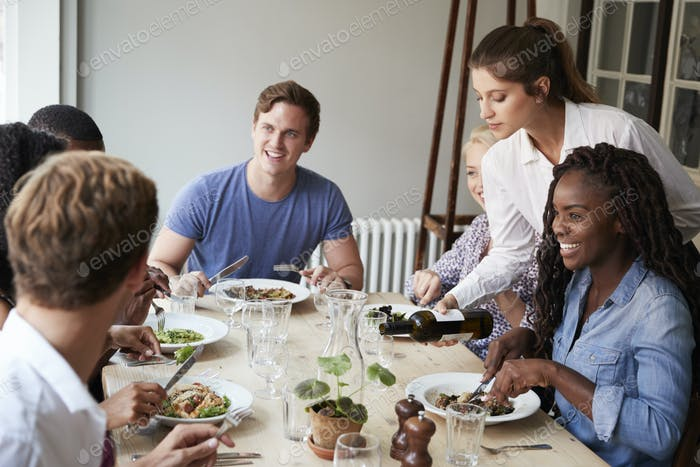 Waitress Pouring Wine For Group Of Friends Enjoying Meal In Restaurant Together