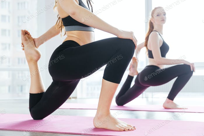 Two women stretching barefoot on pink yoga mat