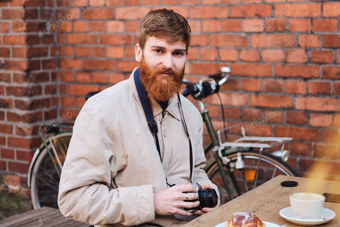 Young attractive photographer intently looking in camera in cafe outdoor