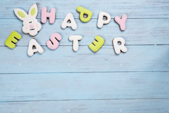 Cookies lettering Happy Easter with rabbit card on wooden blue background.