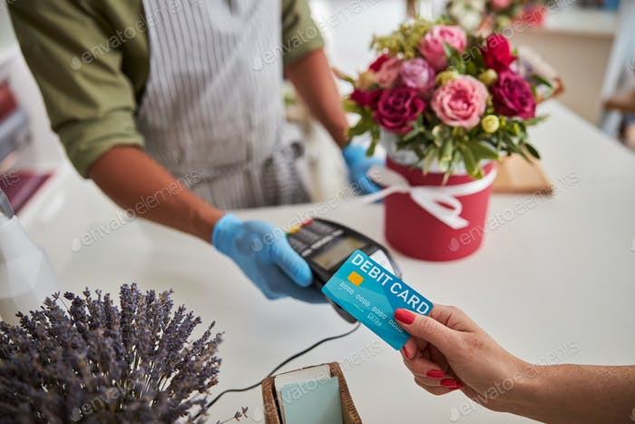 Shopper applying a plastic card to a payment terminal