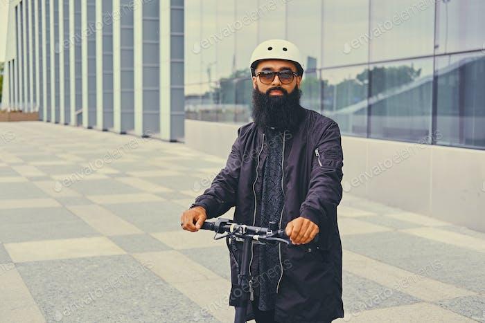 Un hombre posando en scooter eléctrico.