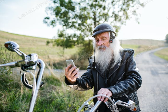 A senior man traveller with motorbike in countryside, taking selfie