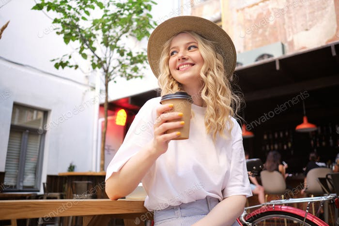 Attractive cheerful casual blond girl in hat joyfully looking away with coffee to go in courtyard