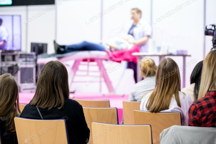 Anonyme Zuschauer hört die Rede des Dozenten auf der Beauty-Industrie Konferenz