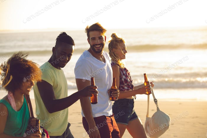 Side view of happy group of diverse friends holding beer bottles and walking together on the beach