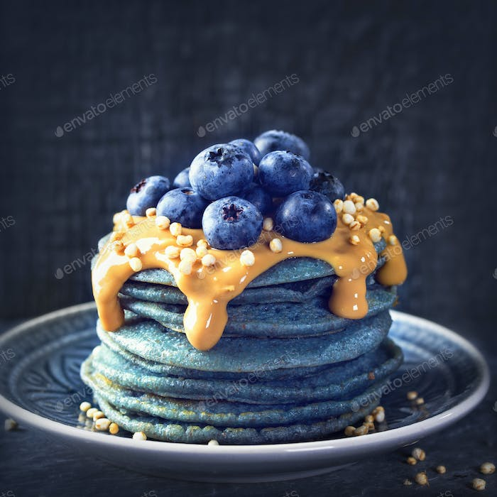 Blue spirulina pancakes topped with peanut butter, blueberries and popped quinoa