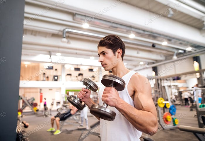 Fit hispanic man in gym working out with weights