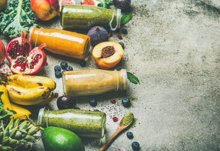Colorful smoothies in bottles with fresh fruits, copy space