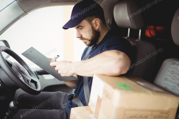 Delivery man sitting in his van while writing on clipboard