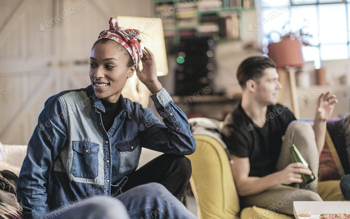 Young woman wearing headscarf and young man holding beer bottle sitting indoors on a sofa, smiling.