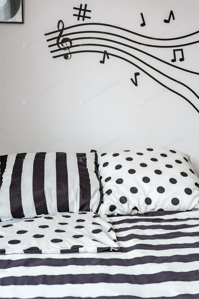 Striped and dotted sheet on bed