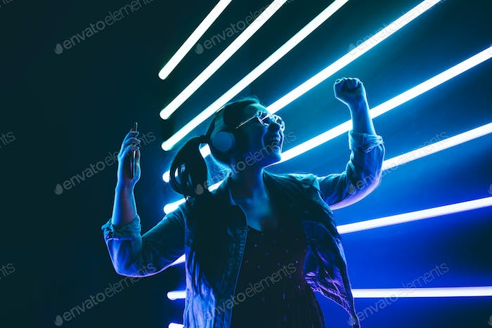 Woman in headphones listening music and dancing in neon light.