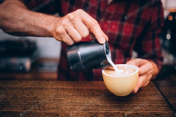 Pouring milk over espresso and creating cappuccino