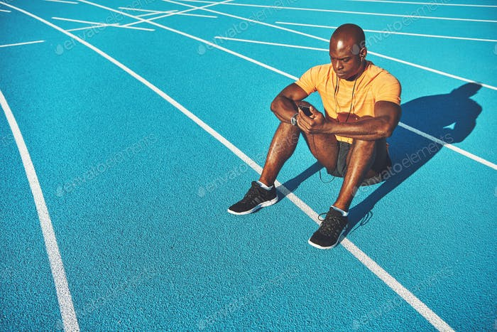 Young runner sitting on a race track listening to music