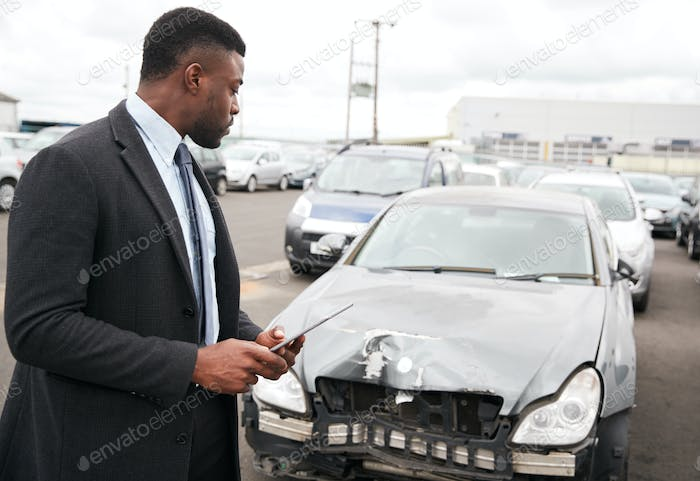 Male Insurance Loss Adjuster With Digital Tablet Inspecting Damage To Car From Motor Accident
