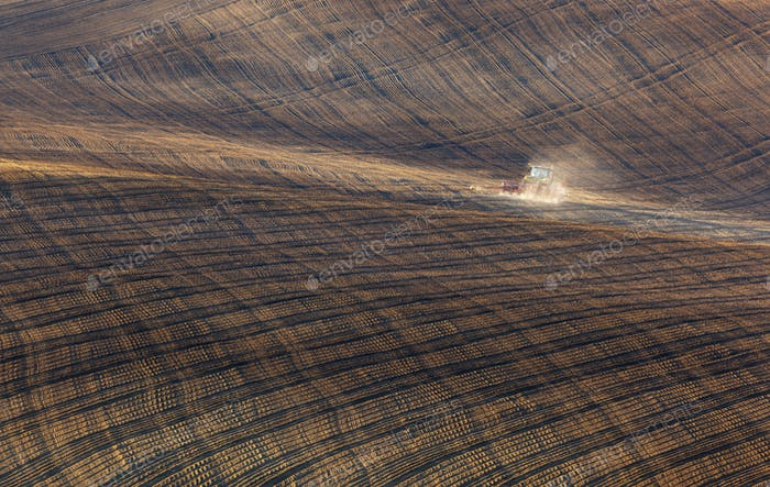 Tractor plowing a stripped field in South Moravia at sunset