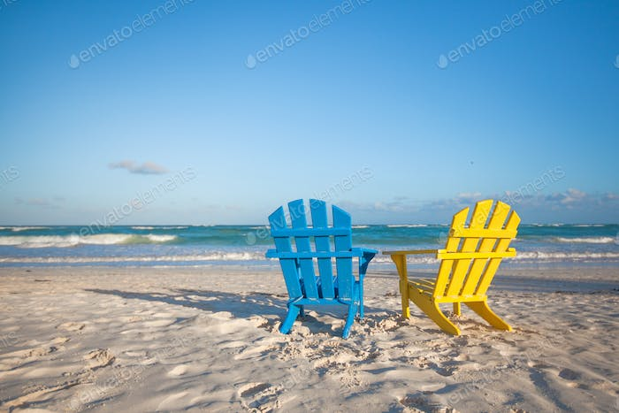 Beach wooden colorful chairs for vacations on tropical beach in Tulum