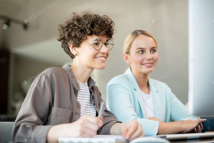 Two happy female colleagues looking at data on computer screen