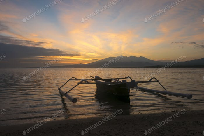 Sunrise with tourist boat and still water on Gili Air Island, In