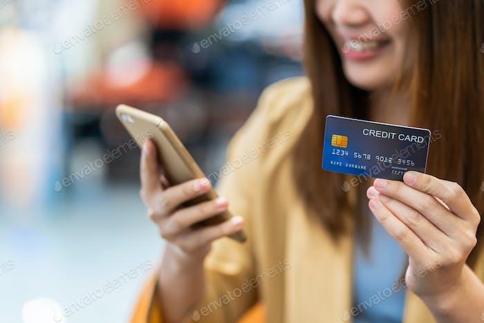 Primer plano mujer asiática mano sosteniendo la tarjeta de crédito y la presentación del teléfono móvil