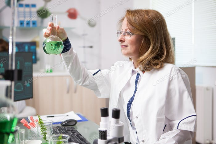 Middle age female biologist in a laboratory looking at chemical test tube