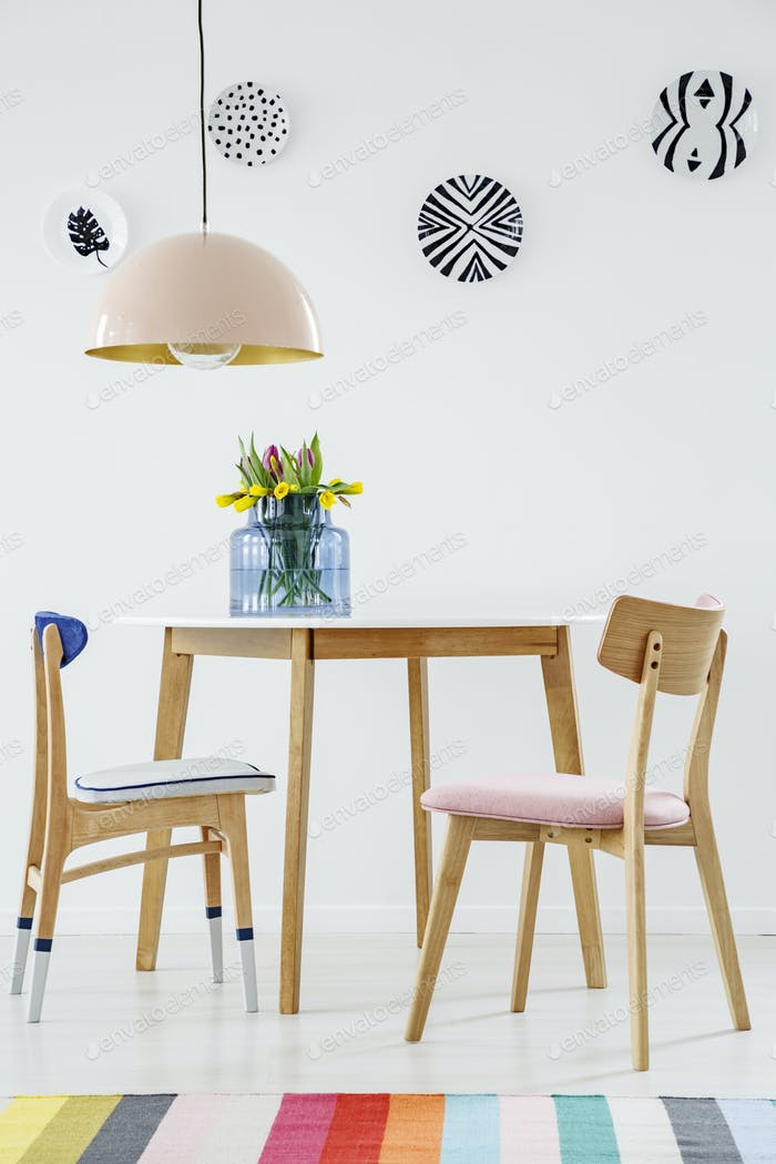 Colorful dining room interior with a table, chairs, striped rug,