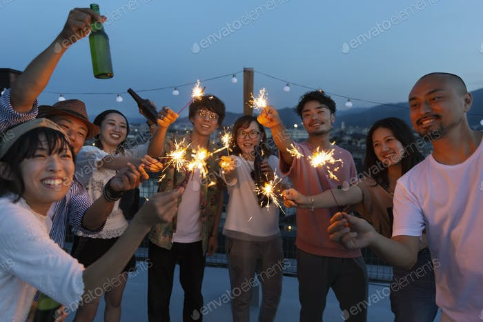 Group of young Japanese men and women with sparklers on a rooftop in an urban setting.