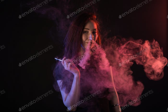 Portrait of asian woman smoking vape or e-cigarette in neon light at black background.