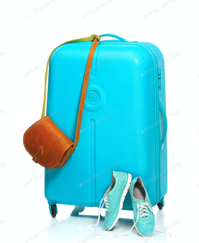 The blue suitcase, sneakers, handbag on white background.