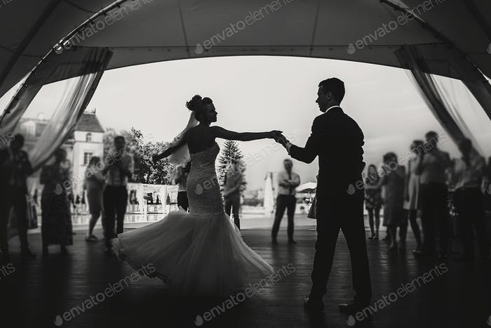 Stylish happy bride and groom gently dancing at wedding reception