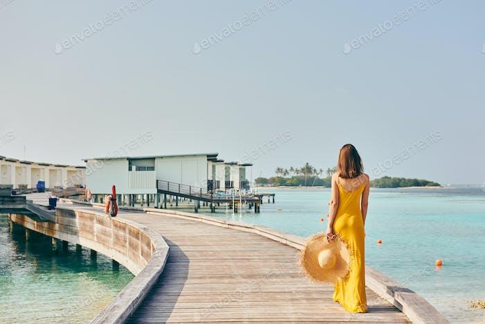 Woman in dress walking on tropical beach boardwalk