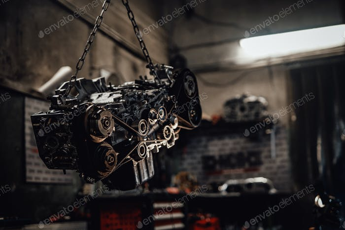 Suspended boxer engine in a dark garage or workshop