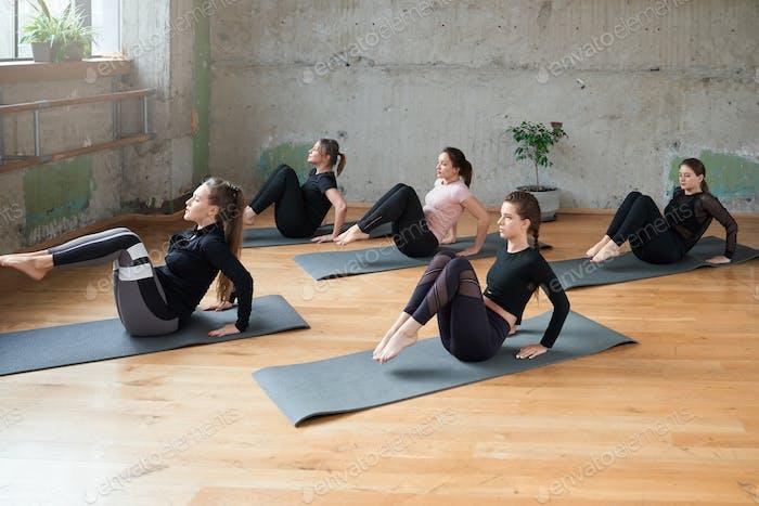 Gruppe von Frauen praktizieren Yoga in Innenräumen