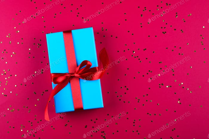 Blue gift box with red ribbon and golden sparkles on red background. Birthday, holiday concept.
