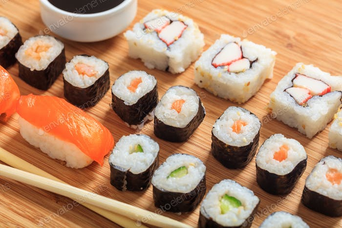 Sushi rolls on wooden surface