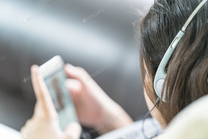 Asian woman listening music from mobile phone-12