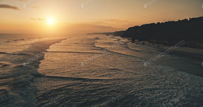 Ocean seascape at sunset light, cliff coast silhouette aerial view. Dark rock sea shore, sand beach