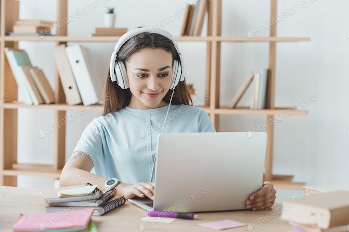 брюнетка студентка учится с ноутбуком и наушниками