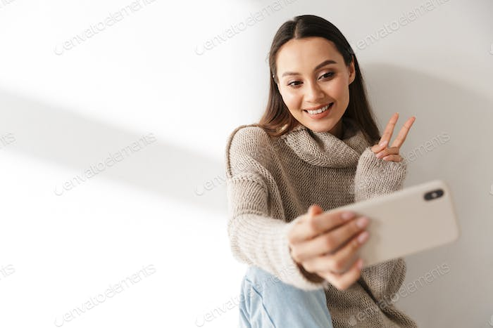 Thumbnail for Image of asian woman gesturing peace sign and taking selfie on cellphone