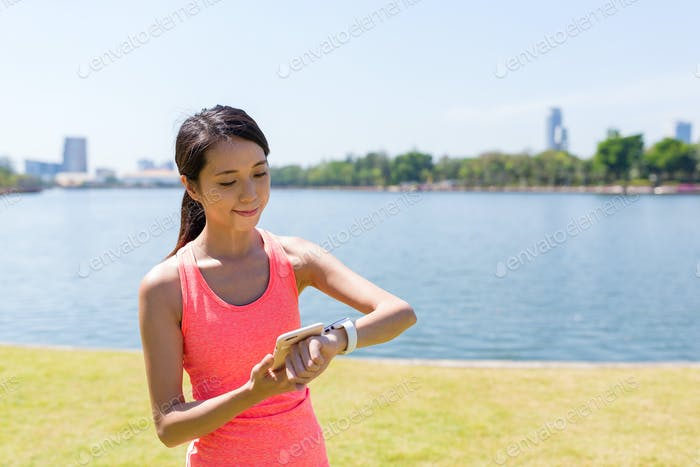 Woman using smart watch at green park