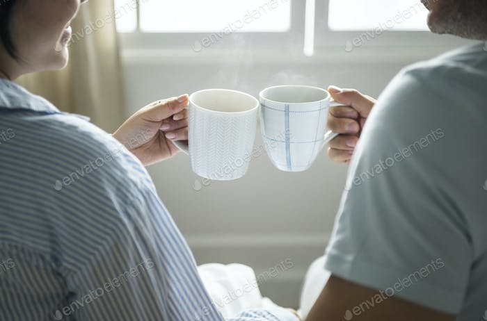 Happy couple celebrating with cups of coffee
