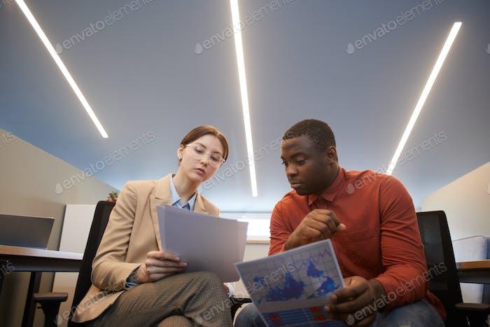 Zwei moderne Geschäftsleute diskutieren Dokumente im futuristischen Interieur