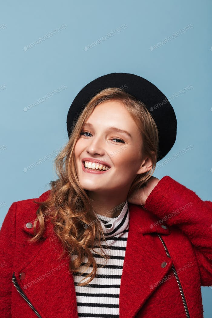 Portrait of cheerful girl with wavy hair in beret and red jacket happily looking in camera