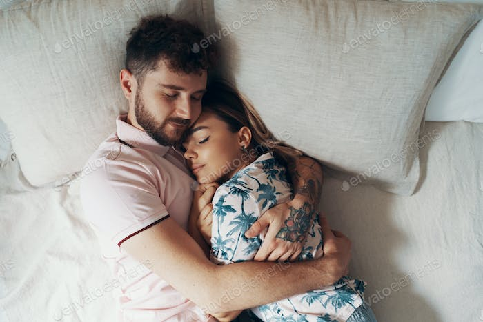 Couple in love is embracing on the bed