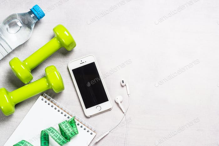 Dumbbells, measuring tape, water and apple top view
