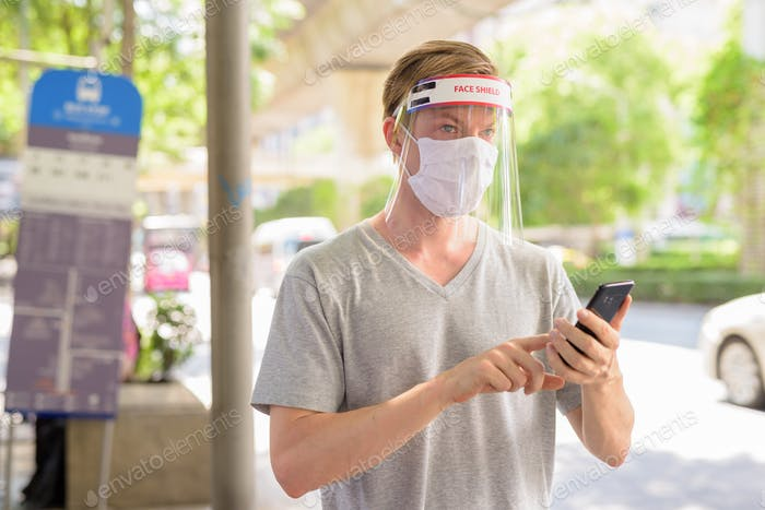 Young man with mask and face shield thinking while using phone at the bus stop